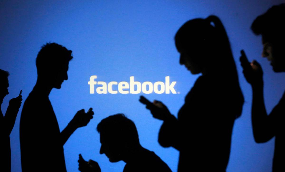 People are silhouetted as they pose with laptops in front of a screen projected with a Facebook logo, in this picture illustration taken in Zenica October 29, 2014. Facebook Inc warned on Tuesday of a dramatic increase in spending in 2015 and projected a slowdown in revenue growth this quarter, slicing a tenth off its market value. Facebook shares fell 7.7 percent in premarket trading the day after the social network announced an increase in spending in 2015 and projected a slowdown in revenue growth this quarter.   REUTERS/Dado Ruvic (BOSNIA AND HERZEGOVINABUSINESS LOGO - Tags: BUSINESS SCIENCE TECHNOLOGY LOGO TPX IMAGES OF THE DAY)